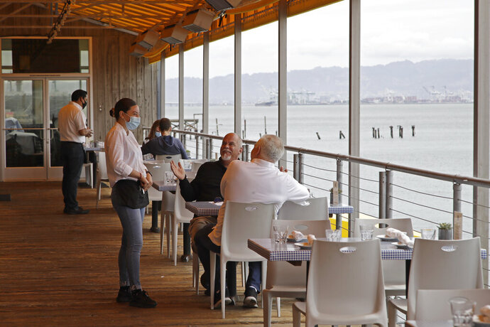 Customers of Mission Rock restaurant interact with their waitress on Friday, June 12, 2020, in San Francisco. Today was the first day outdoor dining is allowed in San Francisco restaurants since the COVID-19 pandemic. (AP Photo/Ben Margot)
