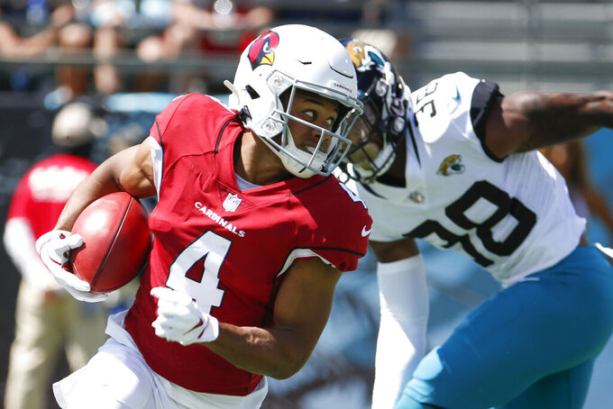 Arizona Cardinals wide receiver Rondale Moore (4) looks for extra room to run as he gets past Jacksonville Jaguars safety Andre Cisco (38) during the first half of an NFL football game, Sunday, Sept. 26, 2021, in Jacksonville, Fla. (AP Photo/Stephen B. Morton)