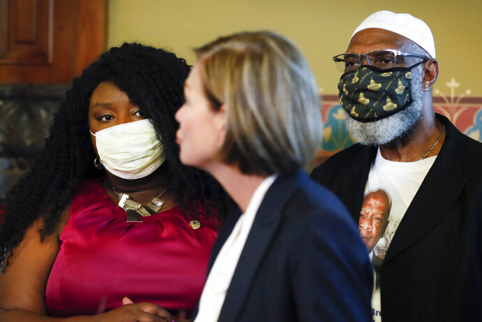 Betty Andrews, president of the Iowa-Nebraska NAACP, left, and State Rep. Ako Abdul-Samad, D-Des Moines, right, listen to Iowa Gov. Kim Reynolds speak after she signed an executive order granting convicted felons the right to vote during a signing ceremony, Wednesday, Aug. 5, 2020, at the Statehouse in Des Moines, Iowa. (AP Photo/Charlie Neibergall)