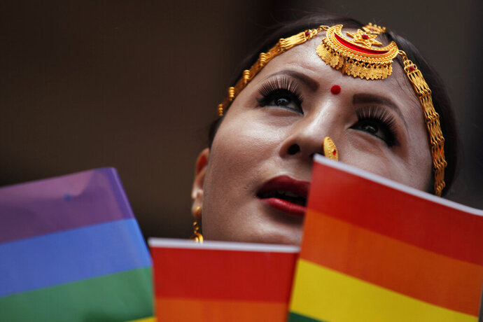 In this Aug. 16, 2019, photo, a participant holds a rainbow flag before marching in a gay pride parade in Kathmandu, Nepal. Nepal seized the lead in equal rights for sexual minorities in South Asia four years ago with a new constitution that forbids all discrimination based on sexual orientation. But activists say progress in equal rights has stalled since the constitution was adopted. (AP Photo/Niranjan Shrestha)