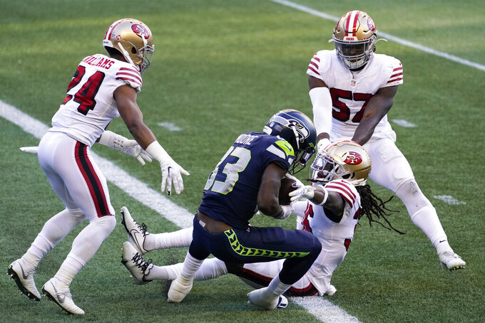 Seattle Seahawks wide receiver David Moore (83) hangs on to the ball as San Francisco 49ers safety Marcell Harris , second from right, reaches for it as Moore scores a touchdown during the second half of an NFL football game, Sunday, Nov. 1, 2020, in Seattle. (AP Photo/Elaine Thompson)