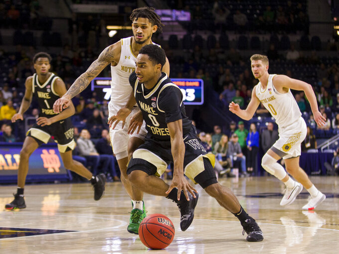 Wake Forest's Brandon Childress (0) drives in next to Notre Dame's Prentiss Hubb during the second half of an NCAA college basketball game Wednesday, Jan. 29, 2020, in South Bend, Ind. Notre Dame won 90-80. (AP Photo/Robert Franklin)