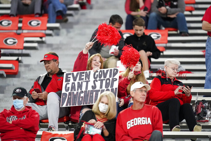 "FILE  - In this Oct. 3, 2020, file photo, a fan holds a sign ""Even COVID can't stop Dawgmation"" before an NCAA college football game, in Athens, Ga. Coaches wearing masks around their chins. Fans not wearing masks at all while cheering from their seats. One school deciding to drop the safety checks it was requiring for those entering the stadium to cut down on long lines. College football is sending plenty of alarming signals at it attempts to get through a tenuous season amid a pandemic. (AP Photo/Brynn Anderson, File)"