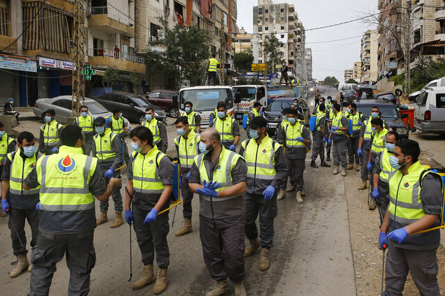 In this Friday, March 27, 2020 photo, members of the Islamic Health Society, an arm of the Iran-backed militant Hezbollah group prepare to spray disinfectant as a precaution against the coronavirus, in a southern suburb of Beirut, Lebanon. Hezbollah has mobilized the organizational might it once deployed to fight Israel or in Syria's civil war to battle the spread of the novel coronavirus. It aims to send a clear message to its Shiite supporters that it is a force to rely on in times of crisis -- particularly after it suffered a series of blows to its prestige. Opponents angrily accuse Hezbollah of helping bring the outbreak to Lebanon, saying it delayed a halt of flights from Iran for weeks after a woman who had just arrived from Iran emerged as Lebanon's first confirmed coronavirus case. (AP Photo/Bilal Hussein)