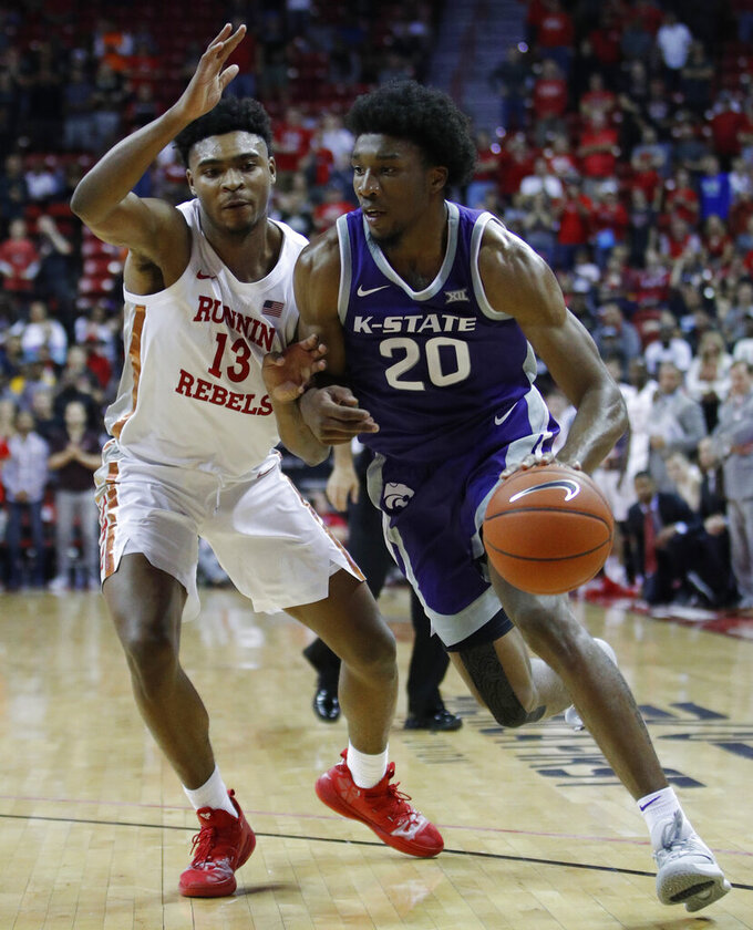 Kansas State's Xavier Sneed (20) drives into UNLV's Bryce Hamilton during overtime of an NCAA college basketball game Saturday, Nov. 9, 2019, in Las Vegas. (AP Photo/John Locher)