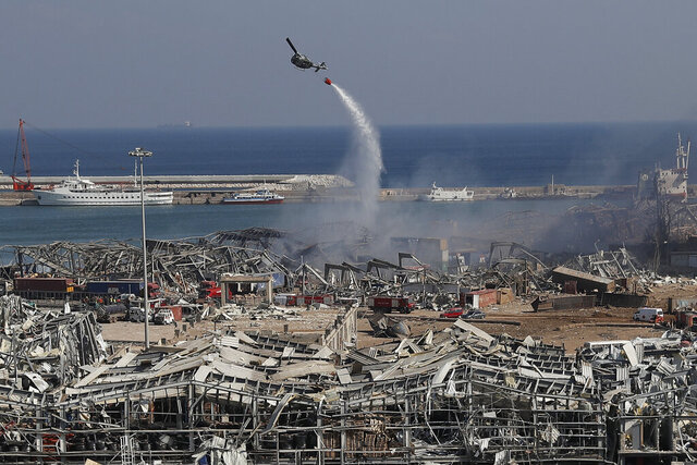 An army helicopter drops water at the scene of Tuesday's massive explosion that hit the seaport of Beirut, Lebanon, Wednesday, Aug. 5, 2020. Residents of Beirut awoke to a scene of utter devastation on Wednesday, a day after a massive explosion at the port sent shock waves across the Lebanese capital, killing dozens of people and wounding thousands. (AP Photo/Hussein Malla)