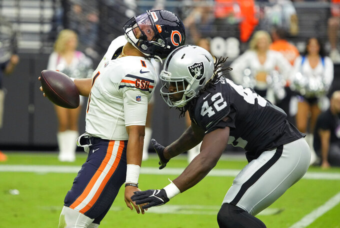 Las Vegas Raiders inside linebacker Cory Littleton (42) holds up from tackling Chicago Bears quarterback Justin Fields (1) after the play was called during the first half of an NFL football game, Sunday, Oct. 10, 2021, in Las Vegas. (AP Photo/Rick Scuteri)