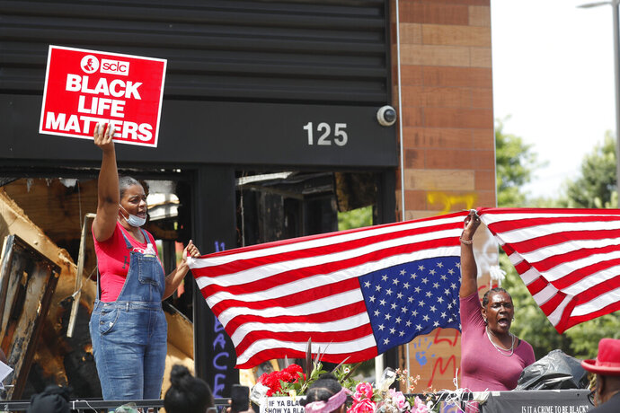 Protesters chant outside a Wendy's restaurant on Tuesday, June 23, 2020, in Atlanta after a funeral for Rayshard Brooks was held. Brooks died after being fatally shot by an Atlanta police officer. (AP Photo/John Bazemore)