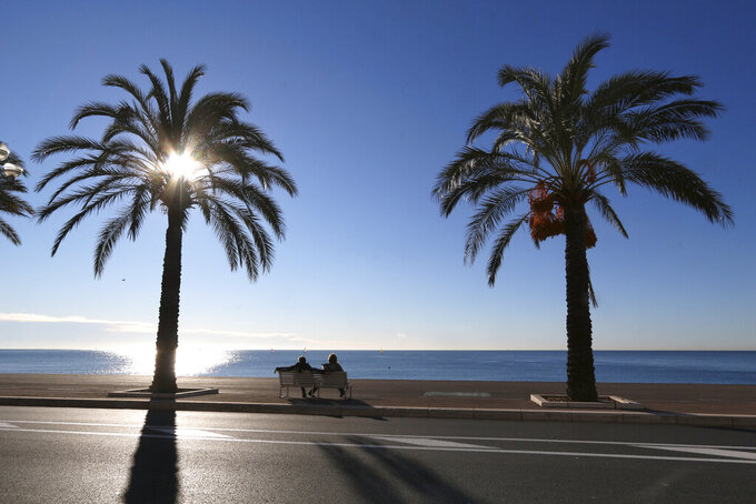 FILE - In this Jan. 16, 2016 file photo people take rest on the Promenade des Anglais, in Nice, southeastern France. Residents of the French Riviera city of Nice won't be allowed to enjoy a walk on the beach on a sunny weekend after authorities have decided to implement a local, temporary lockdown to try to curb the spread of the virus. (AP Photo/Lionel Cironneau, File)