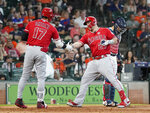 Los Angeles Angels' Mike Trout (27) is congratulated by Shohei Ohtani (17) after hitting a home run as Houston Astros catcher Robinson Chirinos, right, looks down during the sixth inning of a baseball game Sunday, July 7, 2019, in Houston. (AP Photo/David J. Phillip)