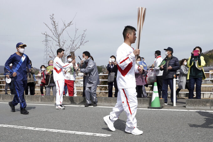 A local torchbearer runs at the torch relay route of the first section of the Fukushima Torch Relay in Naraha, Fukushima prefecture, northeastern Japan, Thursday, March 25, 2021. The torch relay for the postponed Tokyo Olympics began its 121-day journey across Japan on Thursday and is headed toward the opening ceremony in Tokyo on July 23. (AP Photo/Eugene Hoshiko)
