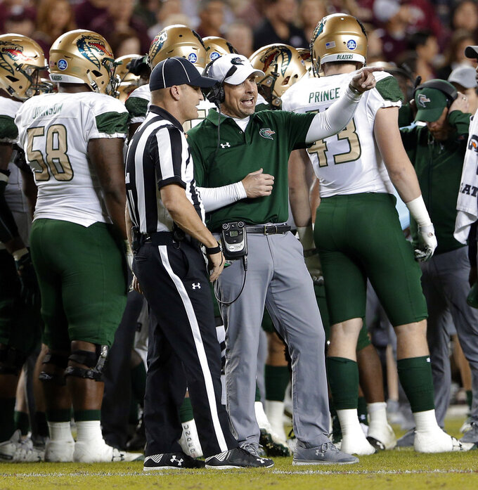 UAB coach Bill Clark talks with official Chad Lorance during the first half of the team's NCAA college football game against Texas A&M on Saturday, Nov. 17, 2018, in College Station, Texas. (AP Photo/Michael Wyke)