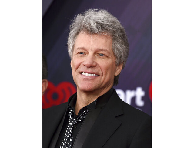 """FILE - This March 11, 2018 file photo shows Jon Bon Jovi at the iHeartRadio Music Awards in Inglewood, Calif. A Florida kindergarten teacher took his virtual classroom to new levels on Monday when rock icon Jon Bon Jovi popped in on a writing lesson about life in the coronavirus quarantine. Last month, the 80s rocker released an incomplete version of """"Do What You Can,"""" a ballad about the nation's battle to contain the virus. He asked fans to submit verses to help complete it. Teacher Michael Bonick sent some of his students' writings about quarantine and Bon Jovi agreed to talk to the class.  (Photo by Jordan Strauss/Invision/AP, File)"""
