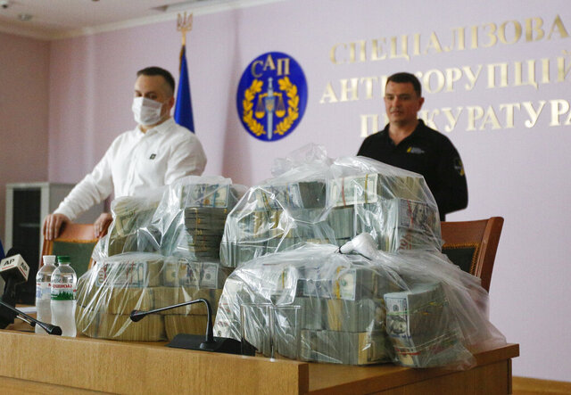 Ukraine's Anti-Corruption Prosecutor Nazar Kholodnytsky, left, and National Anti-Corruption Bureau chief Artem Sytnik at a pile of USD 6 million in plastic bags during a briefing in an anti-corruption prosecutor's office in Kyiv, Ukraine, Saturday, June 13, 2020. Ukrainian authorities say they have intercepted a USD 6 million bribe attempt at dropping a criminal investigation against the head of the Burisma natural gas company where former US Vice President Joe Biden's son once held a board seat. (AP Photo/Efrem Lukatsky)