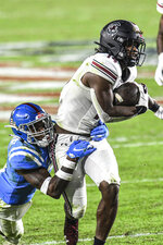 South Carolina running back Deshaun Fenwick (14) is tackled by Mississippi defensive back Jon Haynes during the second half of an NCAA college football game in Oxford, Miss., Saturday, Nov. 14, 2020. (AP Photo/Bruce Newman)