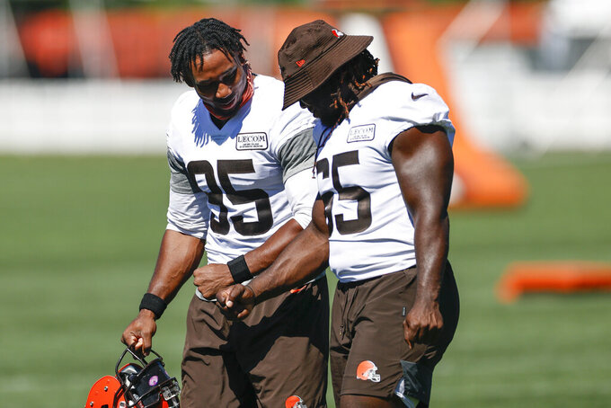 Cleveland Browns defensive end Myles Garrett (95) and defensive tackle Larry Ogunjobi (65) walk across the field during practice at the NFL football team's training facility Thursday, Aug. 20, 2020, in Berea, Ohio. (AP Photo/Ron Schwane)