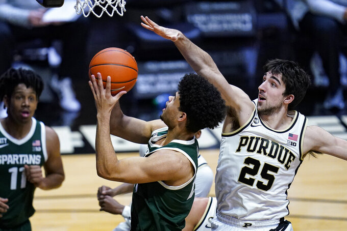 Michigan State forward Malik Hall (25) is fouled by Purdue guard Ethan Morton (25) during the first half of an NCAA college basketball game in West Lafayette, Ind., Tuesday, Feb. 16, 2021. (AP Photo/Michael Conroy)