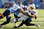 Los Angeles Chargers running back Austin Ekeler (30) is stopped by Tennessee Titans inside linebacker Wesley Woodyard (59) in the first half of an NFL football game Sunday, Oct. 20, 2019, in Nashville, Tenn. (AP Photo/James Kenney)