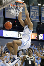 North Carolina's Garrison Brooks (15) dunks against Wofford's Zion Richardson (0) during the first half of an NCAA college basketball game in Carmichael Arena in Chapel Hill, N.C., Sunday, Dec. 15, 2019. (AP Photo/Chris Seward)