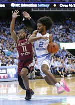 North Carolina's Coby White (2) dribbles while Florida State's David Nichols (11) defends during the first half of an NCAA college basketball game in Chapel Hill, N.C., Saturday, Feb. 23, 2019. (AP Photo/Gerry Broome)