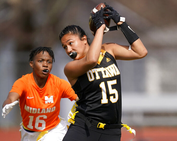 Ottawa receiver Jazlyn Camacho (15) makes a catches while covered by Midland defender E'leseana Patterson (16) during an NAIA flag football game in Ottawa, Kan., Friday, March 26, 2021. The National Association of Intercollegiate Athletics introduced women's flag football as an emerging sport this spring. (AP Photo/Orlin Wagner)