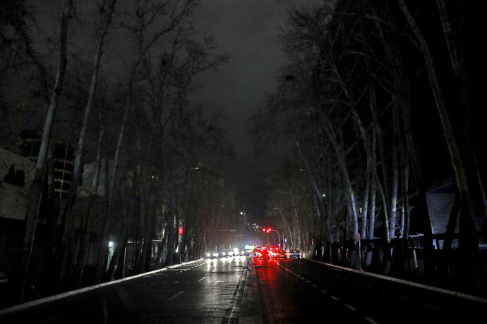 Cars drive on an unlit street during a blackout in Tehran, Iran, Wednesday, Jan 20, 2021. Speculation has gripped social media in Iran that Bitcoin is to blame for a series of recent power blackouts across the country. The government launched a major crackdown on Bitcoin processing centers which use immense amounts of electricity and are a huge burden on the power grid. (AP Photo/Ebrahim Noroozi)