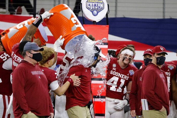 Oklahoma defensive end Ronnie Perkins (7) douses coach Lincoln Riley, center, in the closing seconds of the team's Cotton Bowl NCAA college football game against Florida in Arlington, Texas, Wednesday, Dec. 30, 2020. Oklahoma won 55-20. (AP Photo/Michael Ainsworth)