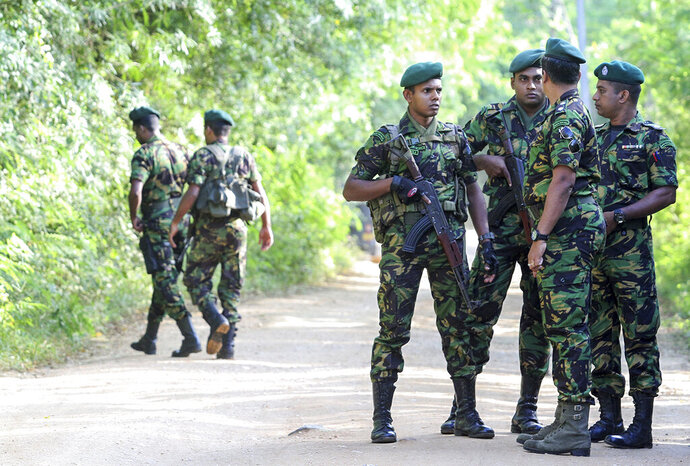 Security personnel patrol outside a polling station during the country's presidential election in Weerawila, Sri Lanka, Saturday, Nov. 16 , 2019. A convoy of buses carrying Muslim voters traveling in northern Sri Lanka was attacked by gunfire and stones, and blocked by burning tires, around midnight on Saturday hours before polls opened in Sri Lanka's presidential election, according to Colombo-based Centre for Monitoring Election Violence. (AP Photo/Chamila Karunarathne )
