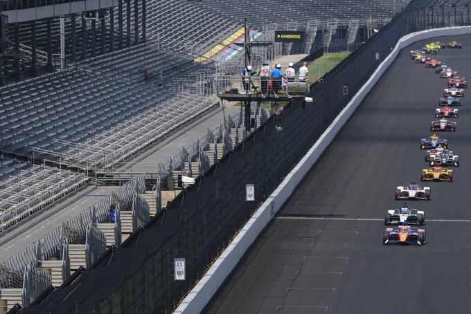 """FILE - Scott Dixon, of New Zealand, leads the pack of cars past empty stands in the early laps of the Indianapolis 500 IndyCar auto race at the Indianapolis Motor Speedway in Indianapolis, in this Sunday, Aug. 23, 2020, file photo. The Indianapolis 500 will be the largest sporting event since the start of the pandemic with 135,000 spectators permitted to attend """"The Greatest Spectacle in Racing"""" next month. Indianapolis Motor Speedway said Wednesday, April 21, 2021, it worked with the Marion County Public Health Department to determine 40% of venue capacity can attend the May 30 race.  (AP Photo/AJ Mast, File)"""