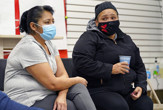 "Graciela Uraga, left, a cleaning lady, and Blanca Cedillos, a nanny, react as they watch Joe Biden's presidential inauguration from the Workers Justice Center, an immigrants rights center, Wednesday, Jan. 20, 2021, in the Sunset Park neighborhood of Brooklyn in New York. Cedillos admitted to being ""nervous"" when the speech started, but after the speech, said she was disappointed Biden didn't mention immigration reform. (AP Photo/Kathy Willens)"