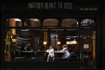 Members of the public are seen in a bar in Manchester's Northern Quarter as strict coronavirus restrictions on England's second-largest urban area, Greater Manchester, will start at midnight, Thursday, Oct. 22, 2020. (AP Photo/Jon Super)