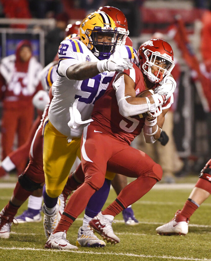 Arkansas running back Rakeem Boyd is tackled by LSU defender Neil Farrell Jr. during the second half of an NCAA college football game, Saturday, Nov. 10, 2018, in Fayetteville, Ark. LSU won, 24-17. (AP Photo/Michael Woods)