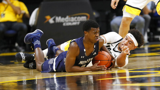 North Florida guard Emmanuel Adedoyin, left, fights for the ball with Iowa forward Cordell Pemsl during the first half of an NCAA college basketball game, Thursday, Nov. 21, 2019, in Iowa City, Iowa. (AP Photo/Charlie Neibergall)