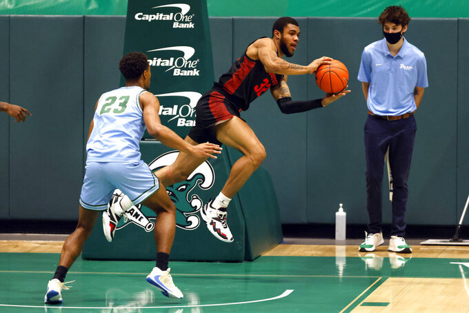 Houston forward Reggie Chaney (32) reaches for the ball in front of Tulane guard R.J. McGee (23) in the first half of an NCAA college basketball game in New Orleans, Thursday, Jan. 28, 2021. (AP Photo/Tyler Kaufman)