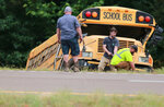 Wrecker crews work on a Benton County School bus that was involved in wreck along U.S. Highway 72 near Walnut, Miss., Tuesday, Sept. 10, 2019, that resulted in the death of the driver and sent several students to the hospital. (Thomas Wells/The Northeast Mississippi Daily Journal via AP)