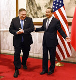 Chinese State Councilor and Foreign Minister Wang Yi, right, shows the way to U.S. Secretary of State Mike Pompeo before a meeting at the Diaoyutai State Guesthouse in Beijing, China Monday, Oct. 8, 2018. (Daisuke Suzuki /Pool Photo via AP)