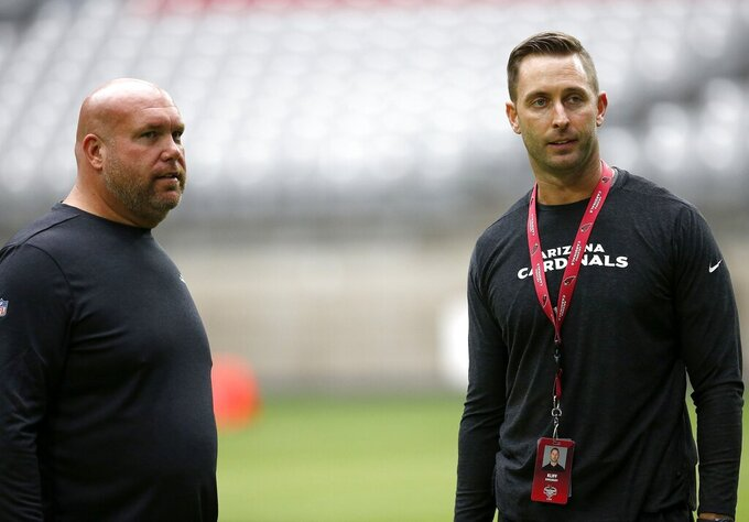 "FILE - In this July 24, 2019, file photo, Arizona Cardinals coach Kliff Kingsbury, right, talks with general manager Steve Keim as players on the NFL football team run sprints in Glendale, Ariz. Keim has been widely praised over the past few weeks after adding elite receiver DeAndre Hopkins in a trade and signing three potential defensive starters. The moves have given Arizona a lot of flexibility for the upcoming draft, eliminating the gaping holes that needed immediate attention. ""We feel like we're free to take the best available pick that comes at the No. 8 spot,"" Kingsbury said. ""That's a tribute to Steve and the job that he's done in the offseason."" (AP Photo/Ross D. Franklin, File)"