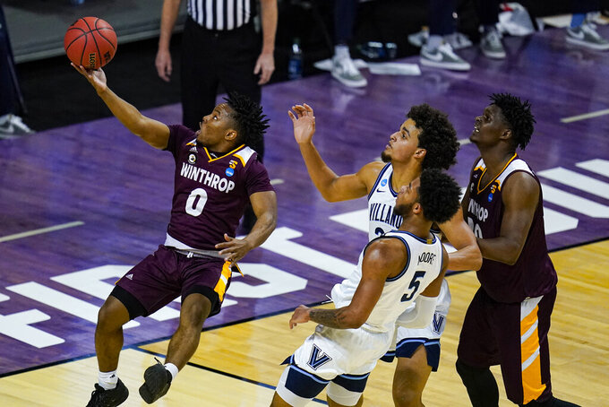 Winthrop guard Russell Jones Jr. (0) shoots in front of Villanova forward Jeremiah Robinson-Earl (24) and guard Justin Moore (5) in the first half of a first round game in the NCAA men's college basketball tournament at Farmers Coliseum in Indianapolis, Friday, March 19, 2021. (AP Photo/Michael Conroy)