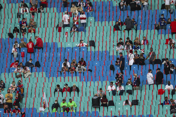 Soccer supporters keep social distance guidelines prior the German Bundesliga soccer match between RB Leipzig and FC Schalke 04 in Leipzig, Germany, Saturday, Oct. 3, 2020. (AP Photo/Michael Sohn)
