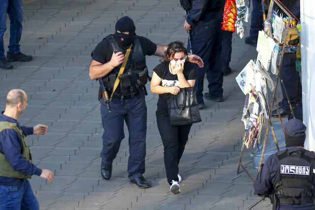 Georgian police officers escorts a woman who escaped from a bank where an armed assailant has taken several people hostage, in the town of Zugdidi in western Georgia, Wednesday, Oct. 21, 2020. The Georgian Interior Ministry didn't immediately say how many people have been taken hostage in the town of Zugdidi in western Georgia, or what demands the assailant has made. Police sealed off the area and launched an operation