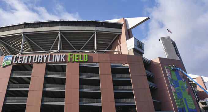 A crew works on a banner featuring Seattle Sounders MLS soccer players outside of CenturyLink Field, Wednesday, March 11, 2020, in Seattle. In efforts to slow the spread of the COVID-19 coronavirus, Washington State Gov. Jay Inslee announced a ban on large public gatherings in three counties in the metro Seattle area. That decision impacts the Seattle Mariners, Seattle Sounders, and the XFL's Seattle Dragons home games. (AP Photo/Stephen Brashear)