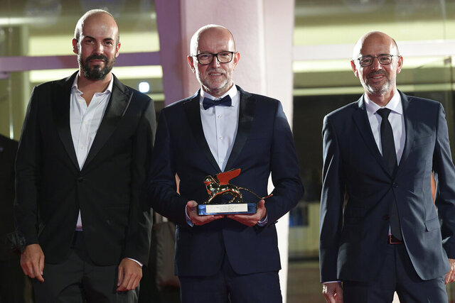 Disney's Marketing Director for Italy, Davide Romani, center, holds the Golden Lion Best Film award for