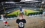 Baseball fans Mark Southard, center left, and his wife Janelle Southard, pose for a photo taken by their son Grayson, 16, as his brother, Gavin, 10, looks on during a tour of Globe Life Field, home of the Texas Rangers baseball team during the first day of public tours in Arlington, Texas, Monday, June 1, 2020. The family drove from their home in Wichita Falls, Texas, to see the team's new home field. (AP Photo/LM Otero)