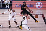 Los Angeles Lakers' Anthony Davis fights for a loose ball with Denver Nuggets' Nikola Jokic (15) and Paul Millsap (4) during the second half of an NBA conference final playoff basketball game Sunday, Sept. 20, 2020, in Lake Buena Vista, Fla. The Lakers won 105-103. (AP Photo/Mark J. Terrill)