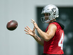 Oakland Raiders quarterback Derek Carr (4) takes a snap during an official team activity, Tuesday, May 21, 2019, at the NFL football team's headquarters in Alameda, Calif. (AP Photo/D. Ross Cameron)