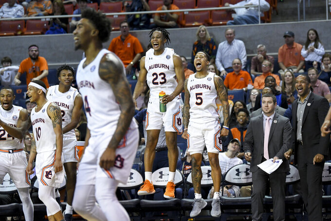 Auburn players cheer from the bench as their subs score in the final seconds against Lipscomb during the second half of an NCAA college basketball game Sunday, Dec. 29, 2019, in Auburn, Ala. (AP Photo/Julie Bennett)