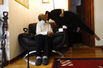 Kimberly Holmes Ross, right, kisses her mother Delores Holmes while celebrating her 83rd birthday, Friday, April 23, 2021, in Evanston, Ill. The Chicago suburb is preparing to pay reparations in the form of housing grants to Black residents who experienced housing discrimination, which Delores Holmes supports. She came to Evanston in 1940s and was an alderwoman in the predominantly Black 5th Ward for 12 years. (AP Photo/Shafkat Anowar)