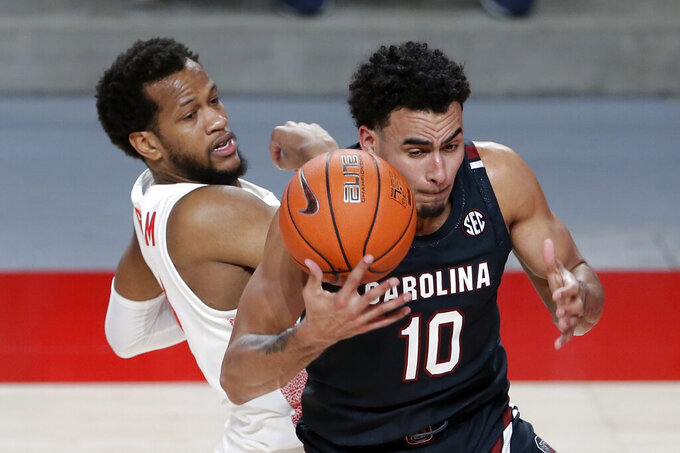 South Carolina forward Justin Minaya (10) bobbles a rebound in front of Houston forward Justin Gorham (4) during the first half of an NCAA college basketball game Saturday, Dec. 5, 2020, in Houston. (AP Photo/Michael Wyke)