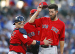Boston Red Sox catcher Christian Vazquez, left, calls for someone to come and check out starting pitcher Rick Porcello, right, after Porcello was knocked over by a batted ball during the second inning of a spring training baseball game against the Chicago Cubs on Monday, March 25, 2019, in Mesa, Ariz. (AP Photo/Sue Ogrocki)