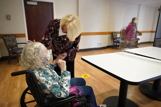 FILE - In this March 18, 2021, file photo, Mary Claire Lane, 86, left, a resident at Hellenic Nursing and Rehabilitation Center, in Canton, Mass., is greeted by her daughter Anne Darling, of Attleboro, Mass., center, during a visit,  at the nursing home, in Canton. Nursing homes have to publicly disclose their vaccination rates for flu and pneumonia, but there's no similar mandate for COVID-19 shots. (AP Photo/Steven Senne, File)